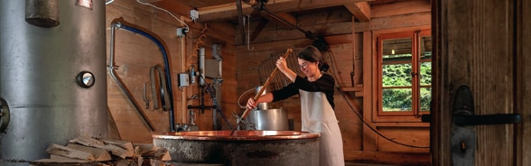Woman making cheese with a traditional cheese vat