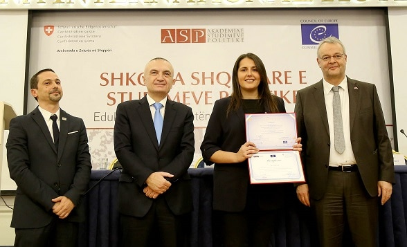 Albania's President Ilir Meta and Swiss Ambassador Adrian Maître handing out diploma certificates to new graduates from the School of Political Studies.