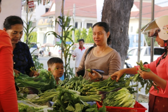Families at a local produce shop in Phnom Penh, Cambodia.