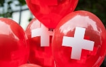 Red balloons with the white Swiss cross