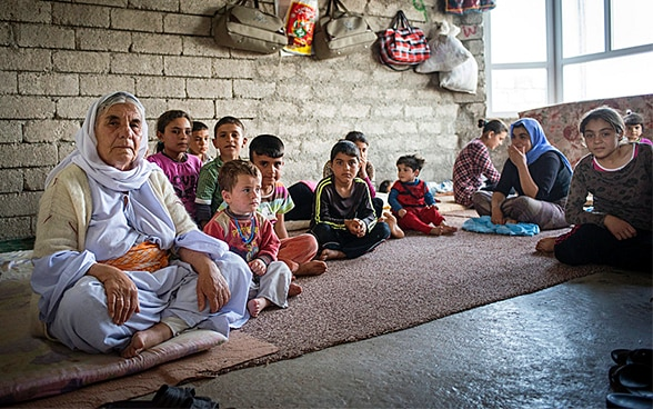 Yazidi women sit in a room in unfinished building being shared with a total of over 100 refugees near Duhok, Iraqi Kurdistan, Northern Iraq.