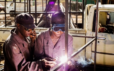A man instructs a woman to use a welding device.