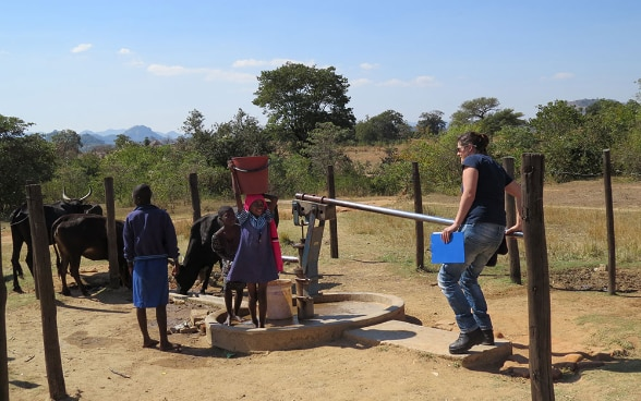 Children gather round an SHA expert as she pumps water from a well.