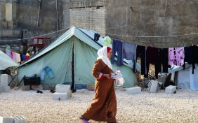 A woman refugee walks in front of a tent.