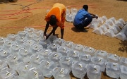 People being provided with water from a tank in South Sudan