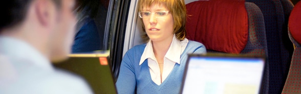 A man and a woman working at a computer in a train