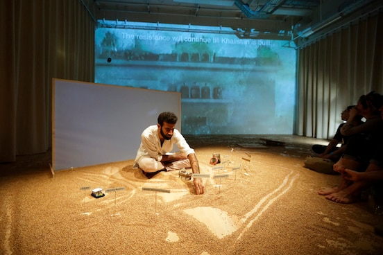 A man sitting on a stage drawing in sand, with the audience sitting on the floor very close by. A film is being shown on a screen behind the artist