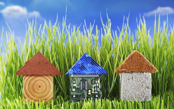 Three small toy houses in a row, on grass.