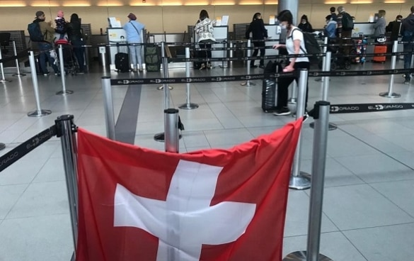 In the hall of the airport of Bogotà a Swiss flag hanging at the check-in counter indicates the flight to Switzerland.