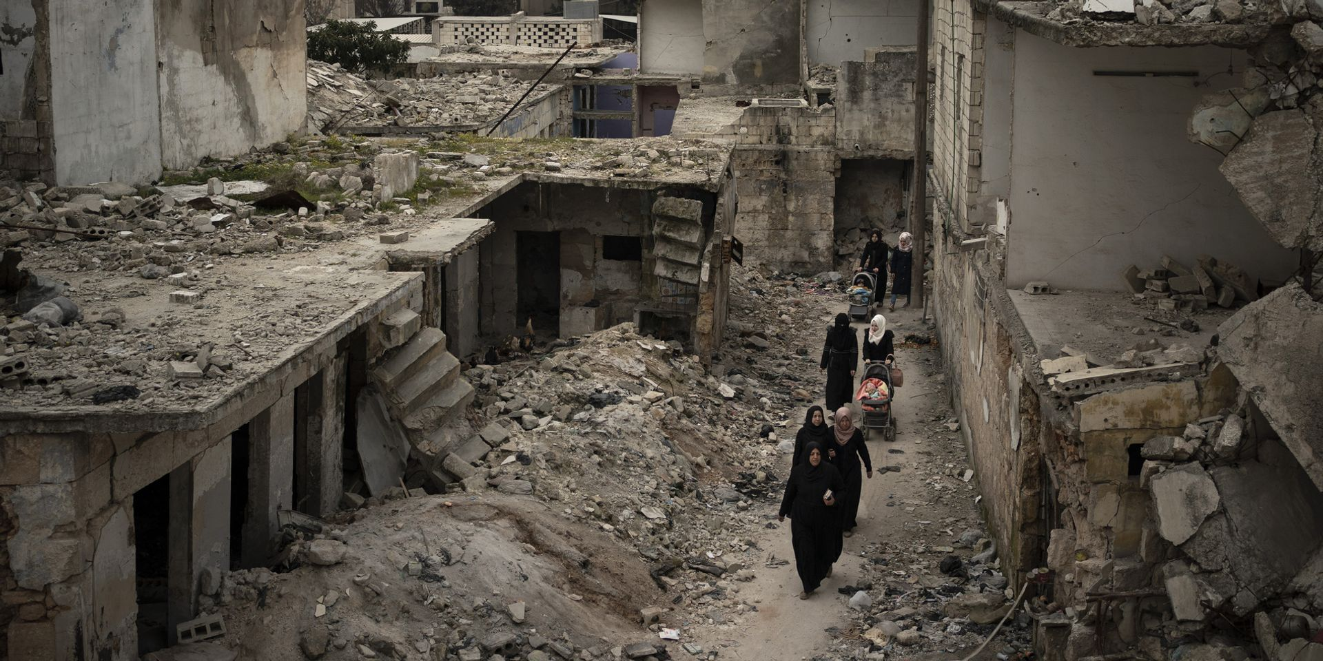 Women walk with prams through the rubble of a street with collapsed houses.