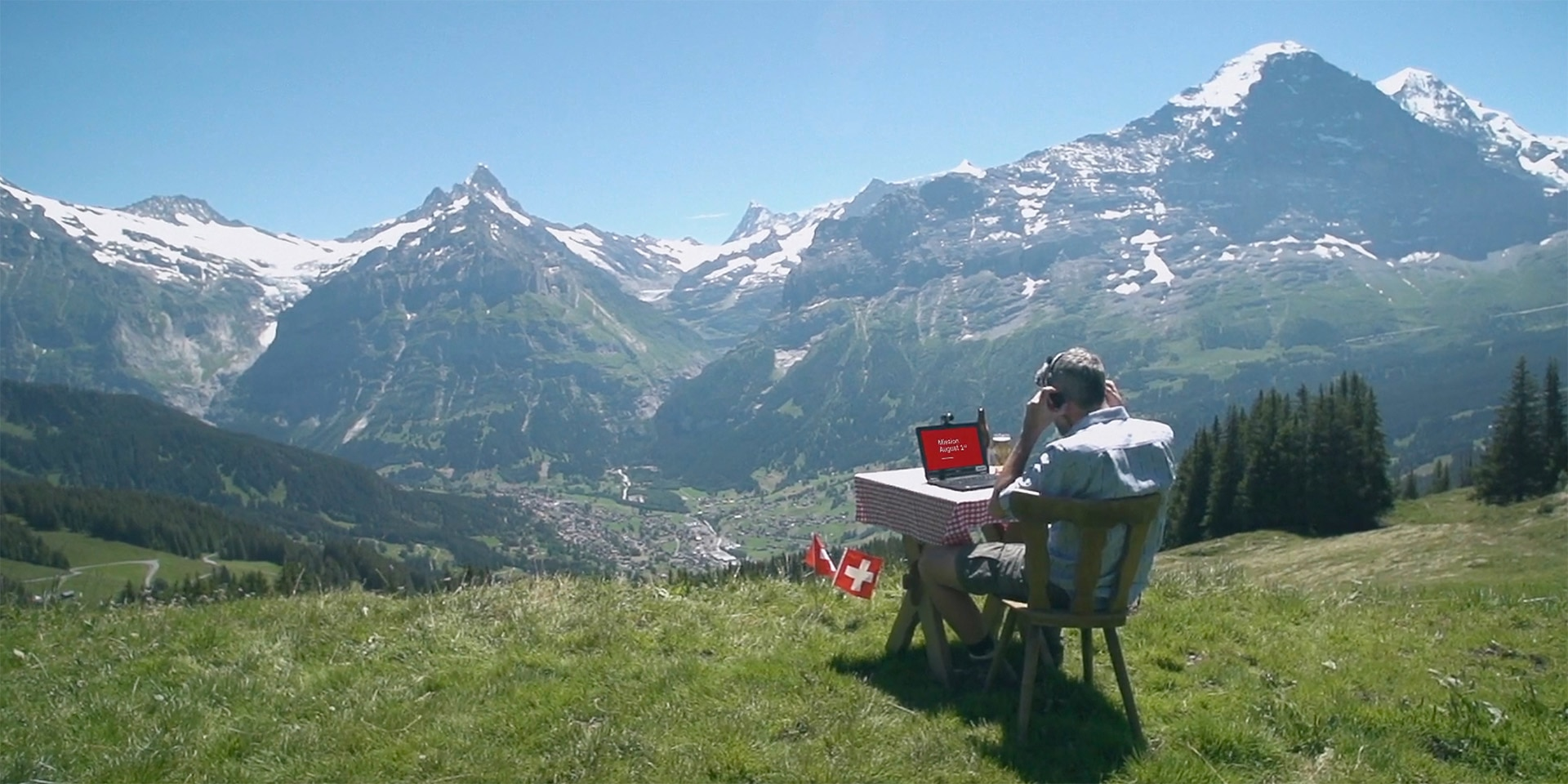 A man is sitting at a table in the Alps, working on a laptop.