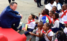 Federal Councillor Ignazio Cassis on his Africa trip smiling as sits on the floor with a group of children.