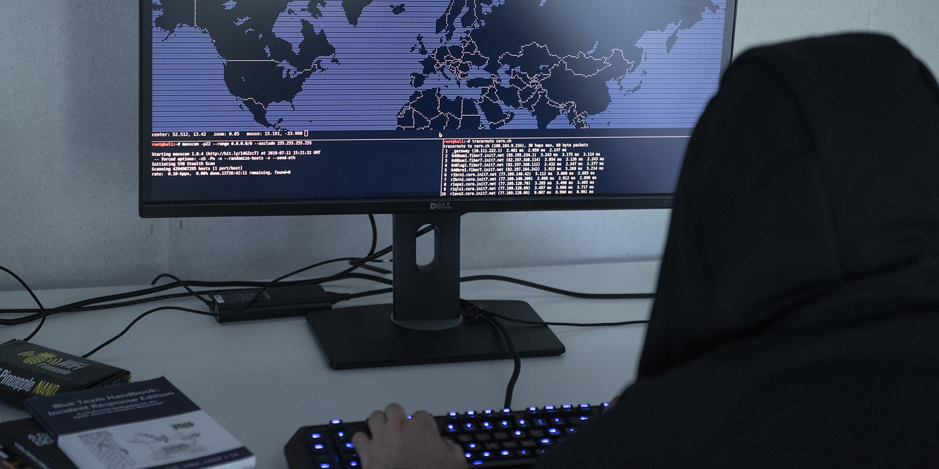 To symbolise cybercrime, a man in a hooded sweatshirt sits in front of a computer displaying a map of the world and modifies programming codes.