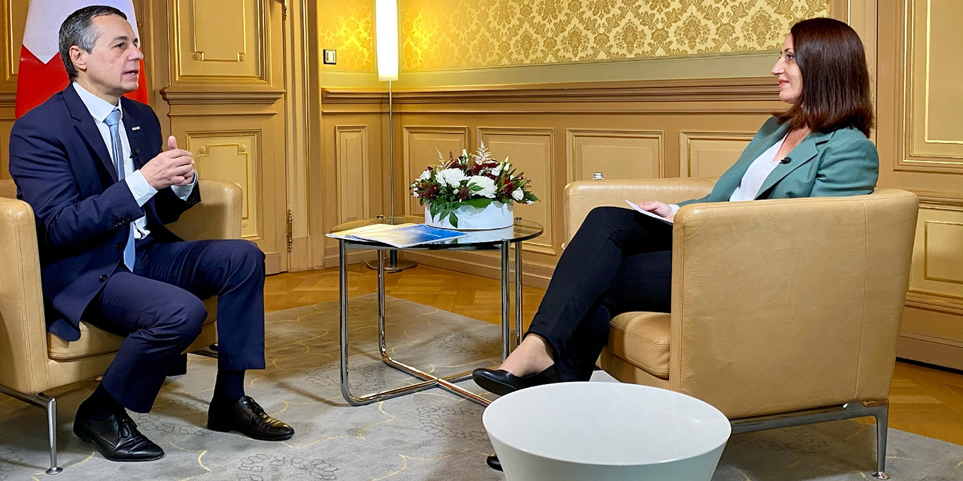 Federal Councillor Ignazio Cassis sits in a chair and talks to the presenter during an interview.