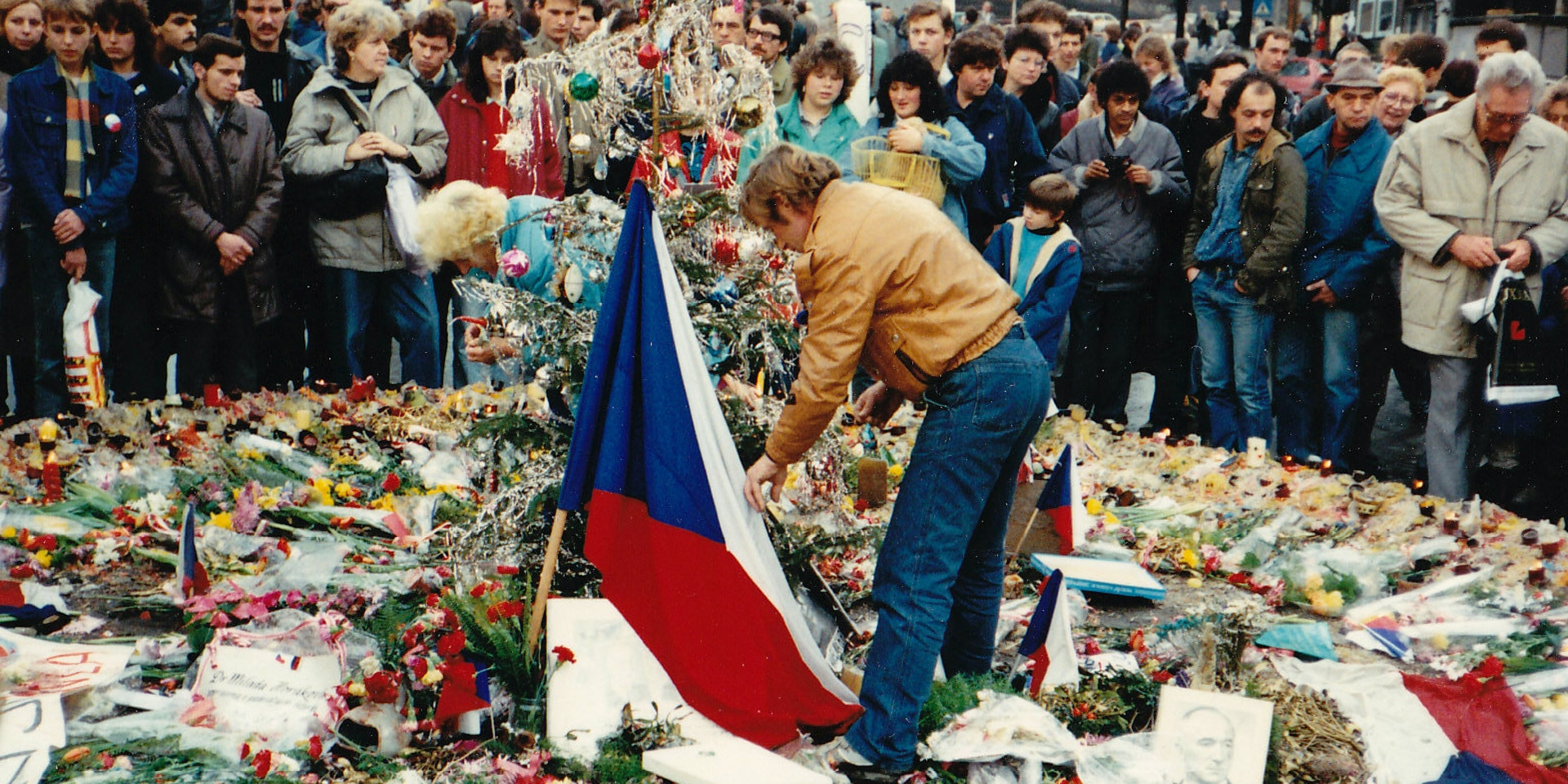 Surrounded by a crowd, Václav Havel lays flowers on Wenceslas Square.