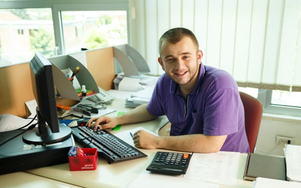 A young man sitting in an office in front of a computer.