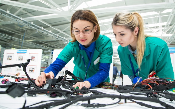 Two young women checking cables.