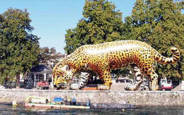 A larger-than-life blown-up plastic jaguar at the waterside. © Art for The World