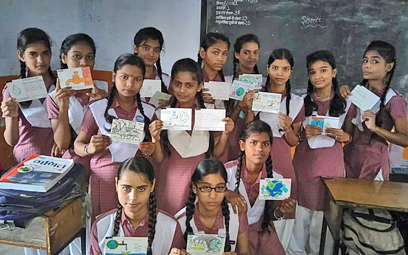 A class of girls in India proudly showing off the postcards they drew and wrote on as part of the Guinness world record attempt on the Jungfraujoch.