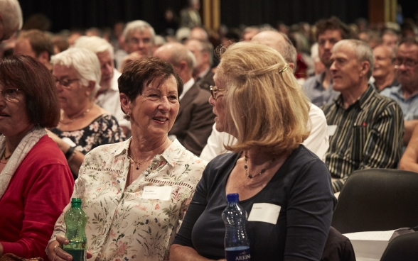 Two annual conference participants in the audience having an animated discussion.