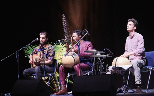 Three musicians with their instruments on stage, sitting in front of microphones. The musician in the middle is singing.