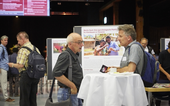 Two participants by a standing table at the Bernexpo Festhalle. Behind them is the exhibition from the different partner organisations.