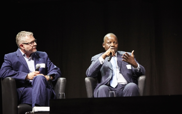 Mansour N'Diaye sitting on stage and speaking into a microphone. Dominique Guenat sitting next to him and listening attentively.
