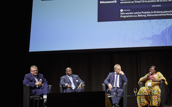 Mansour N'Diaye, Dominique Guenat, Pierre-André Page, Mariane Nguerassem and moderator Melanie Pfändler sitting on stage. In the background is a screen with a presentation of questions from the audience.