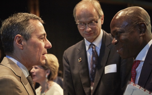 Ignazio Cassis and Gilbert F. Houngbo in discussion. Pio Wennubst is standing nearby.