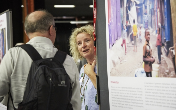 A participant talking to a stand supervisor at the exhibition of the partner organisations.