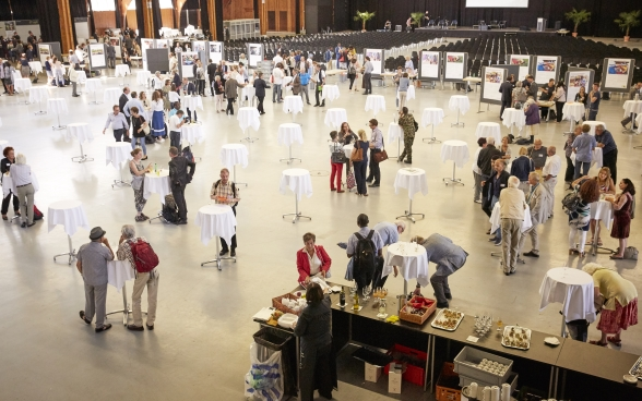 A bird's-eye view of the Bernexpo Festhalle where participants are talking, eating and drinking around a number of standing tables.
