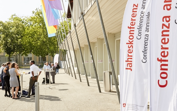 The Bernexpo Festhalle from outside. Colourful flags are hanging in front of the doors and there are white posters bearing the word 'Jahreskonferenz' in all the official languages and English.