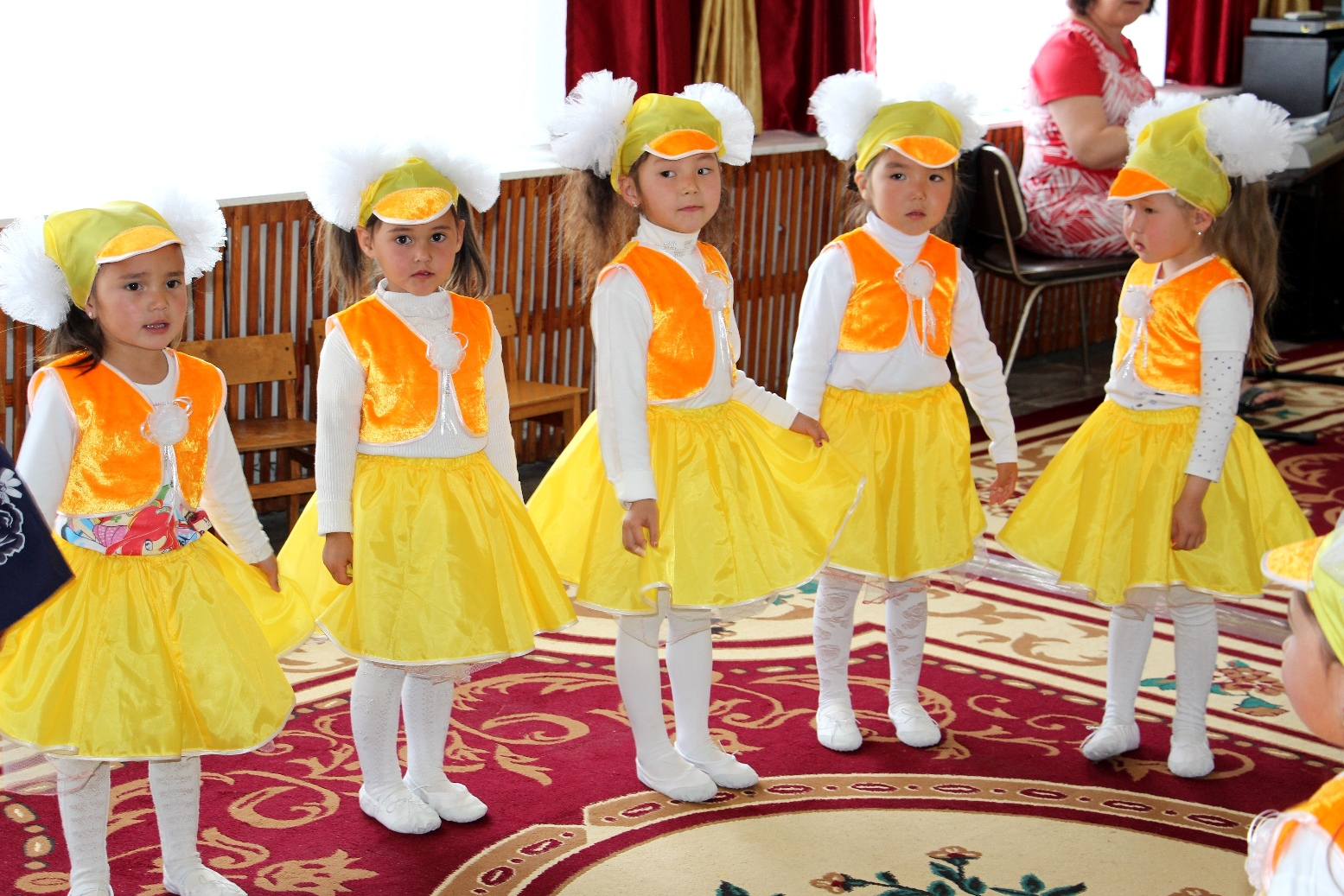 Five young girls in yellow costumes at the opening ceremony of the new kindergarten