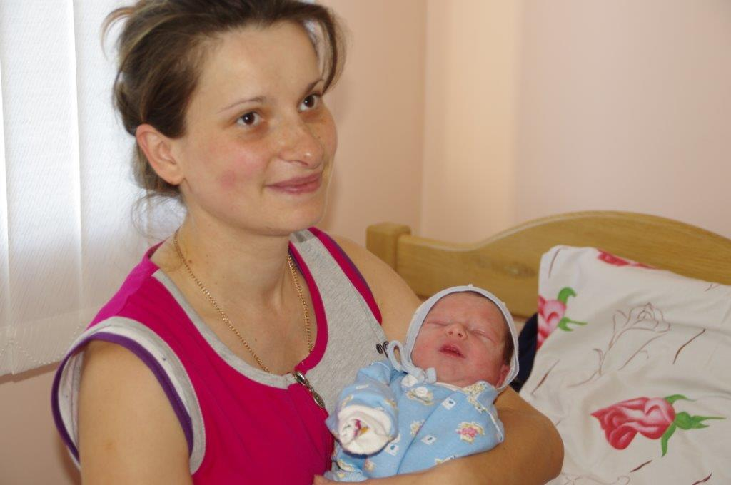 A smiling mother cradling her newborn baby in her arms.