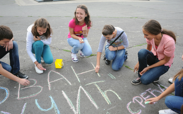 Young people drawing in the schoolyard with chalk.