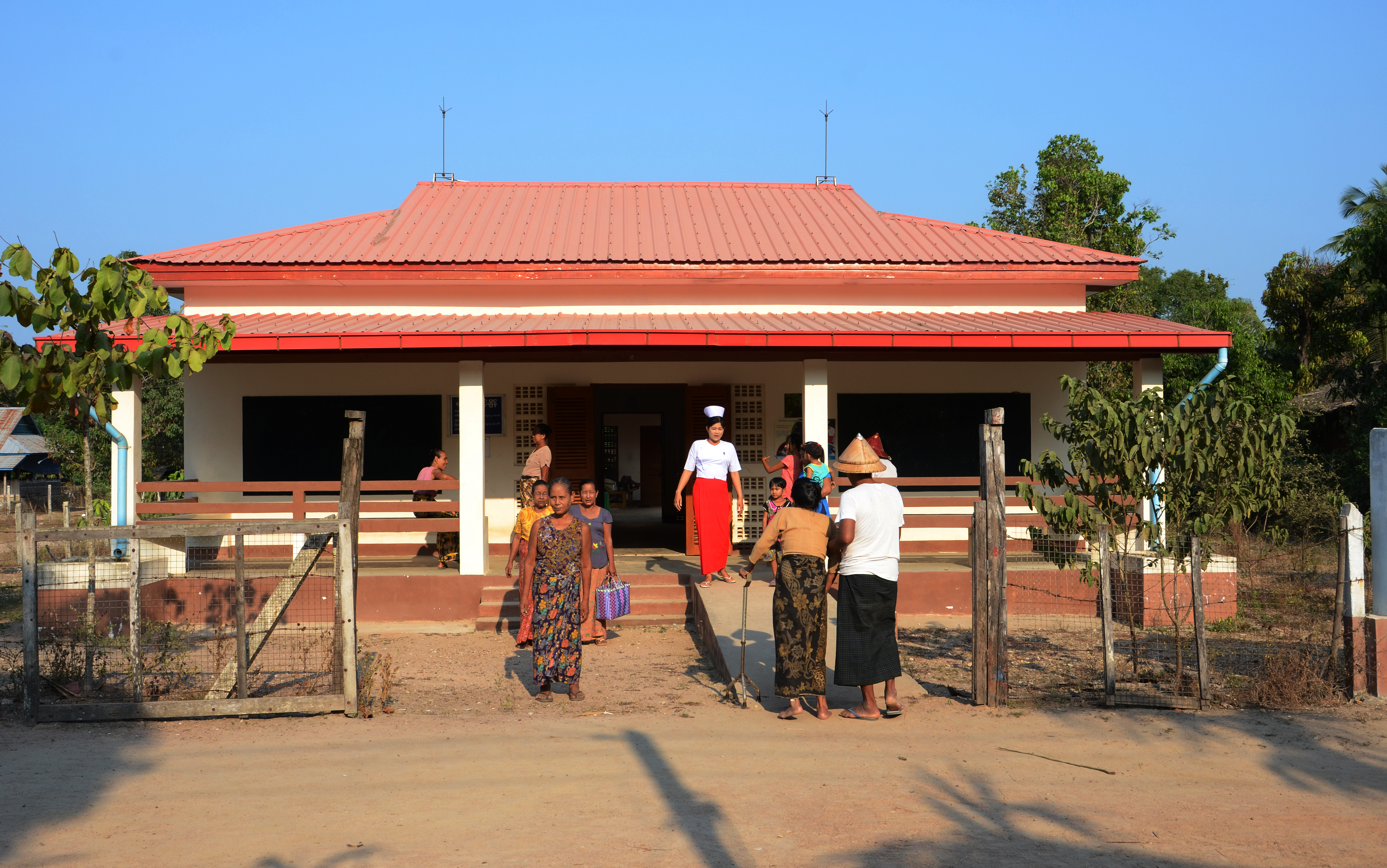 A nurse receives patients at the entrance to a health centre.