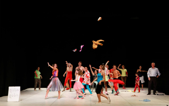 Dancers on a stage in colorful dresses throw clothes in the air.