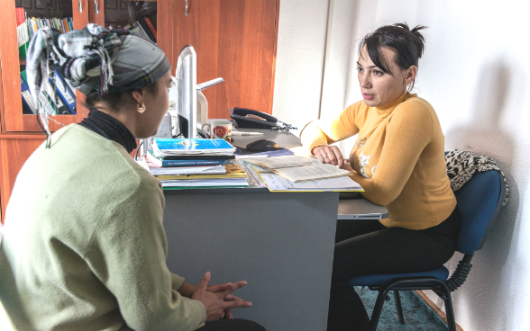 A lawyer sits at her desk and discusses with a woman.