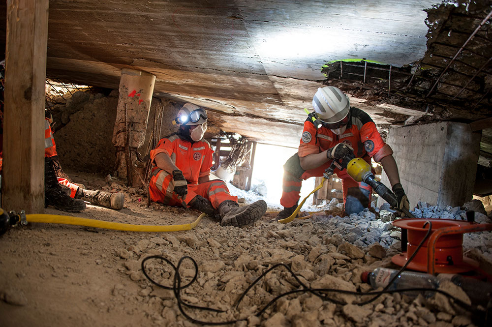 Three rescuers training in rubble.