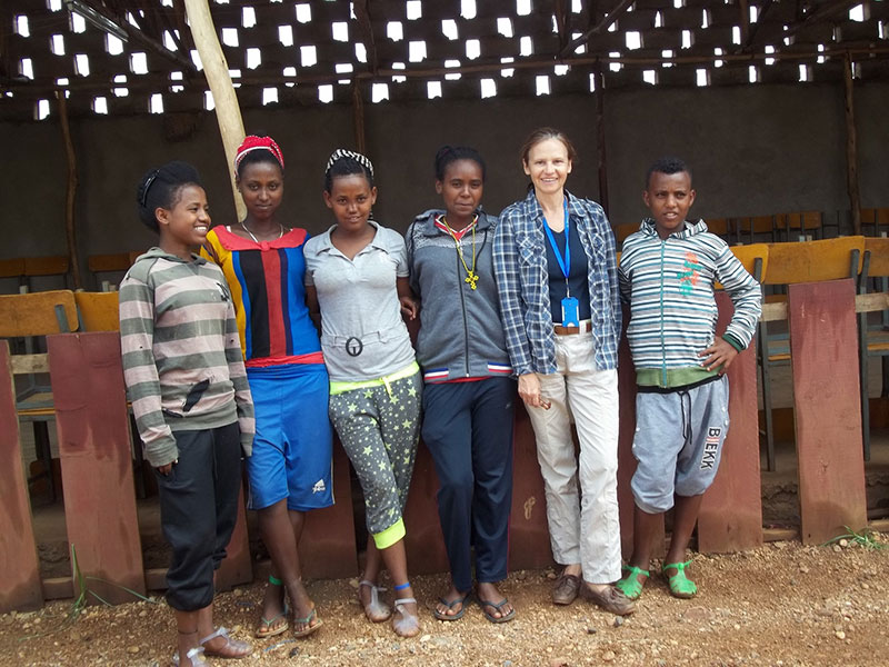 an SDC specialist standing with five African adolescents.