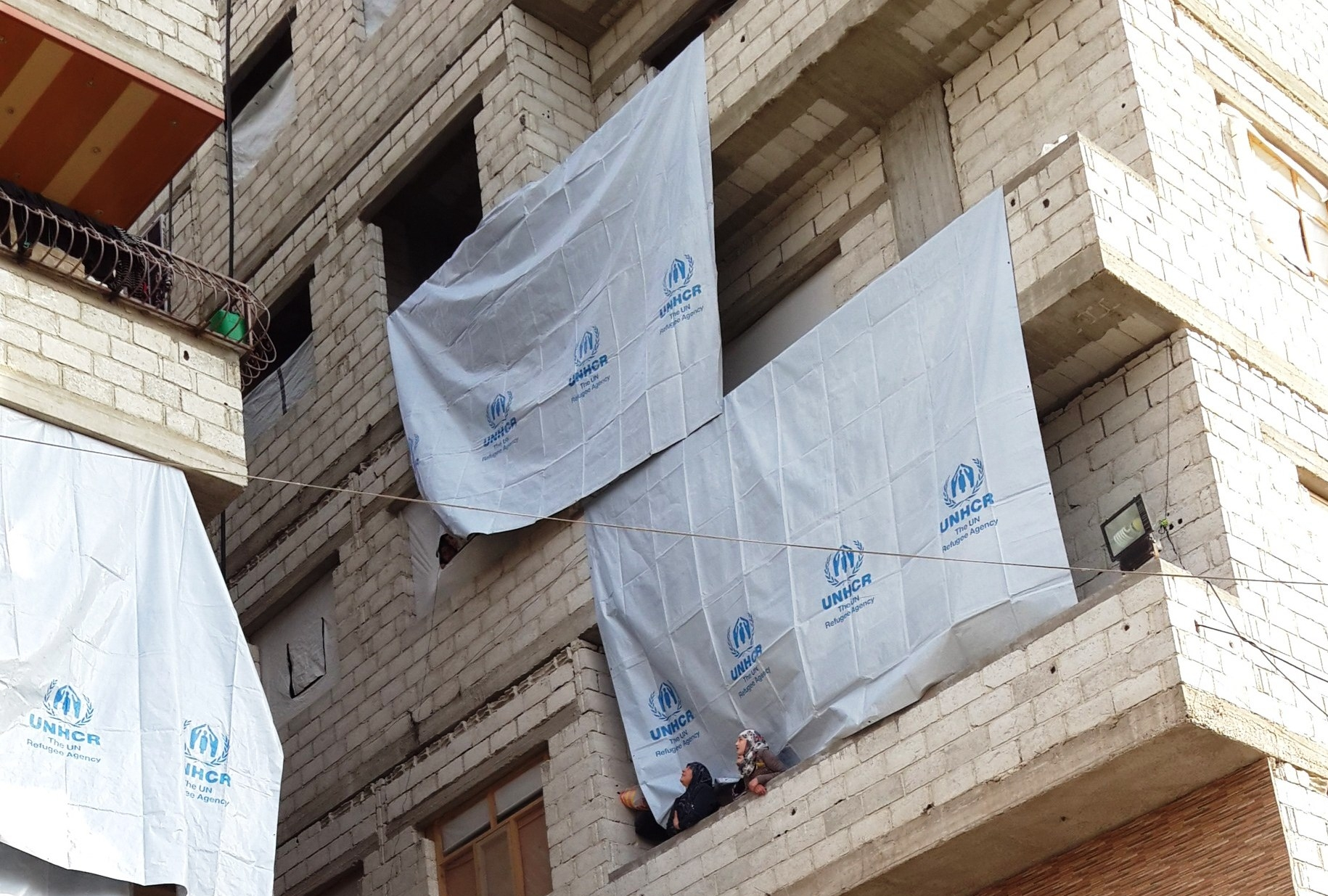 Two women wearing veils on a balcony in a building draped with UNHCR flags.