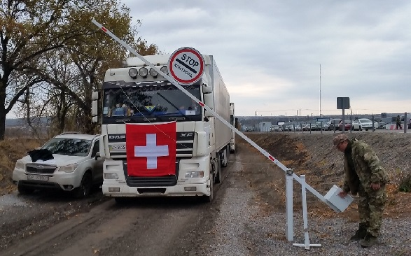 A soldier raises a barrier, opening the way for a Swiss Humanitarian Aid lorry.