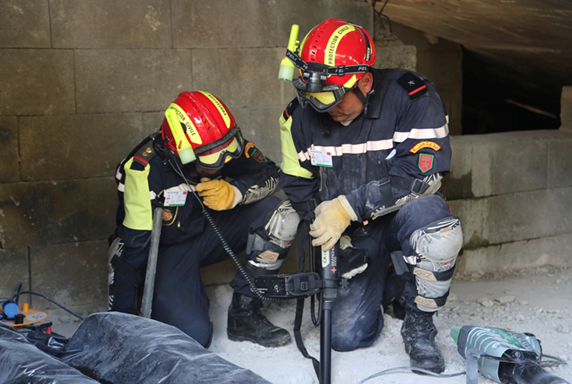 Two rescue workers training inside a destroyed building with a search device.
