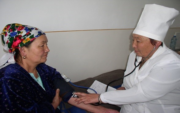 : A woman doctor examining a woman patient.