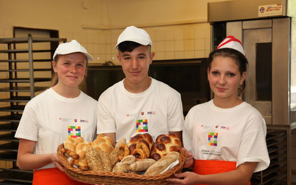 Three baker apprentices showing the bread they have made.