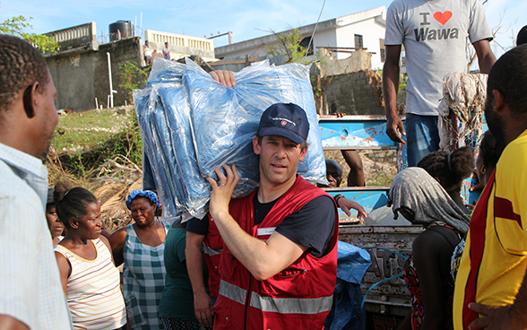 A Swiss expert surrounded by Haitians hands out tarpaulin sheets.