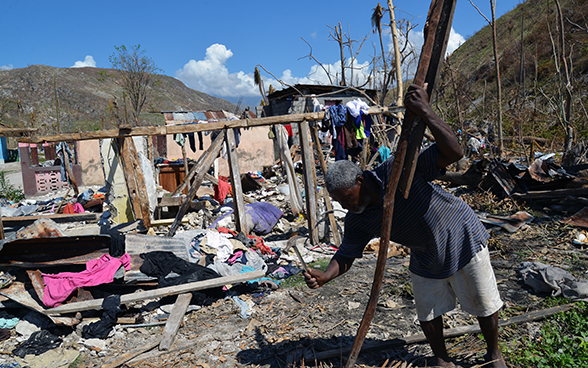 A man holding a hammer stands in front of his destroyed home.