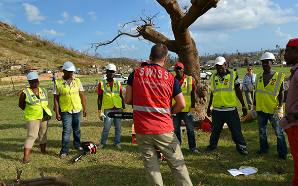 A Swiss expert holding a chainsaw instructs members of the Haitian civil protection authorities.