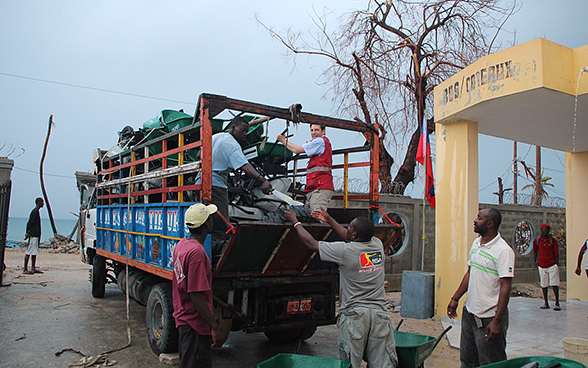 Men unload a lorry filled with wheelbarrows and tools.