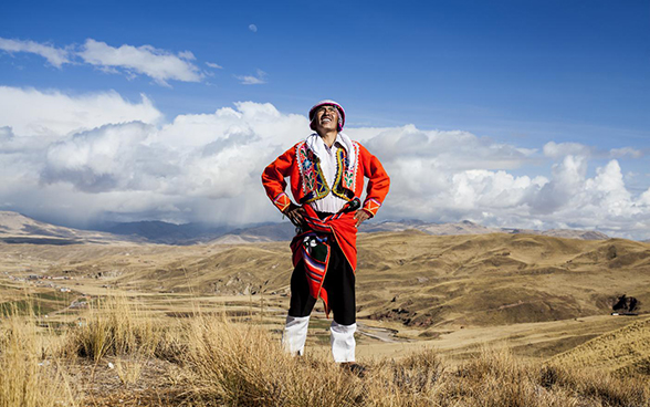 A man in traditional Peruvian clothing stands in open countryside in the Peruvian highlands, and looks up at the sky.